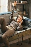 Femme s'étendant sur le divan et la musique de écoute Photographie stock