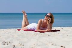 Femme s'étendant sur le sable près de la mer parlant par le téléphone photos stock