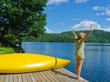 Femme s'étirant avant la plongée outre du dock dans le lac image stock