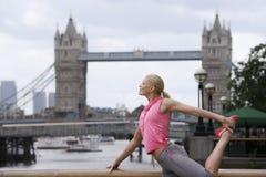 Femme s'étirant contre le pont de tour en Angleterre Photographie stock