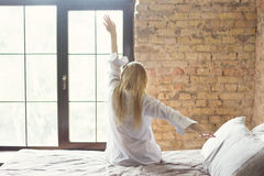 Femme s'étirant dans le lit après s'être réveillé Photos libres de droits