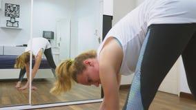 Femme s'étirant près du miroir à son appartement Le concept d'un mode de vie sain, pas un sport professionnel clips vidéos