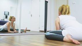 Femme s'étirant près du miroir à son appartement Le concept d'un mode de vie sain, pas un sport professionnel banque de vidéos