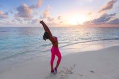 Femme s'étirant sur la plage Image stock
