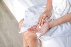Femme s'appliquant hydratant la crème/lotion sur des mains images libres de droits