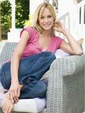 Femme s'asseyant à l'extérieur sur le sourire de patio Image libre de droits