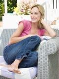 Femme s'asseyant à l'extérieur sur le sourire de patio Photo stock