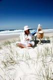 Femme s'asseyant à la plage Image stock