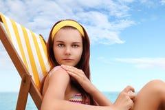 Femme s'asseyant à la plage vous avez mis la protection solaire Photographie stock libre de droits