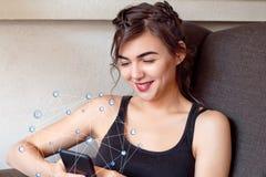 Femme s'asseyant à la table avec la tasse de café utilisant son smartphone Image libre de droits