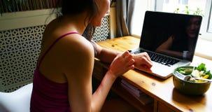 Femme s'asseyant à la table et à l'aide de la montre intelligente banque de vidéos