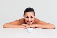 Femme s'asseyant à la table et regardant sur le pot crème images stock