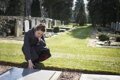 Femme s'asseyant à la tombe photo libre de droits