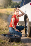 Femme s'asseyant à la voiture cassée et essayant de changer le pneu crevé Image stock