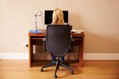 Femme s'asseyant au bureau fonctionnant à l'ordinateur dans le siège social Photographie stock