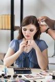 Femme s'asseyant au styliste, création de regard image stock