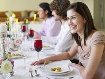 Femme s'asseyant avec des amis au dîner Photo stock