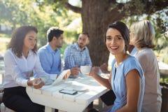 Femme s'asseyant avec des amis dans le restaurant extérieur Photo stock