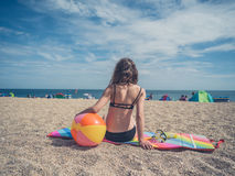Femme s'asseyant avec du ballon de plage Photographie stock libre de droits