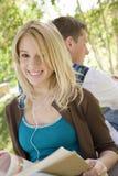 Femme s'asseyant avec l'ami au campus d'université Photographie stock libre de droits