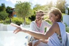 Femme s'asseyant avec l'ami en dehors du pointage à quelque chose riant Photo libre de droits