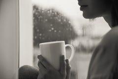 Femme s'asseyant avec la tasse de thé par la fenêtre Photos libres de droits