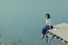 Femme s'asseyant avec le livre sur la table de conseil près du lac Photos libres de droits