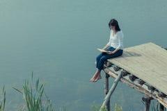Femme s'asseyant avec le livre sur la table de conseil près du lac Photographie stock libre de droits