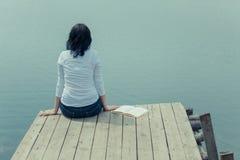 Femme s'asseyant avec le livre sur la table de conseil près du lac Photos stock