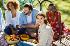 Femme s'asseyant avec ses amis en parc Photographie stock libre de droits