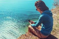 Femme s'asseyant avec une boussole sur la côte Photographie stock