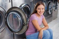 Femme s'asseyant contre des machines à laver photographie stock