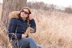 Femme s'asseyant contre l'arbre dans le domaine tenant le wildflo sélectionné frais photo stock