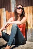 Femme s'asseyant contre le mur images stock