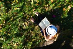 Femme s'asseyant dans l'herbe affichant un livre Photographie stock