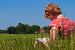 Femme s'asseyant dans l'herbe raeding un livre Photos libres de droits