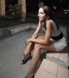 Femme s'asseyant dans l'obscurité photo stock