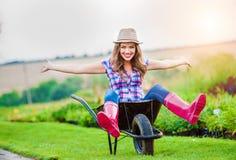 Femme s'asseyant dans la brouette dans le jardin vert ensoleillé photographie stock