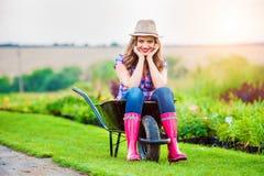 Femme s'asseyant dans la brouette dans le jardin vert ensoleillé image libre de droits