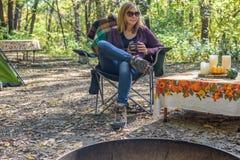 Femme s'asseyant dans la chaise de camping avec la tasse de café au terrain de camping images libres de droits