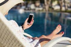 Femme s'asseyant dans la chaise de plate-forme par la piscine et à l'aide du téléphone portable Image stock