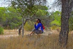 Femme s'asseyant dans la forêt Photographie stock