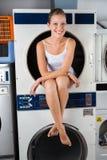 Femme s'asseyant dans la machine à laver images stock