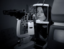 Femme s'asseyant dans la machine d'opticien Images stock