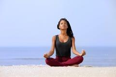 Femme s'asseyant dans la pose de yoga à la plage Image libre de droits