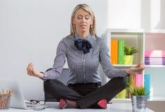 Femme s'asseyant dans la pose de yoga de lotus sur le bureau dans le bureau Images libres de droits