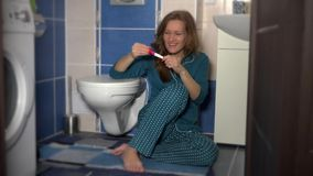 Femme s'asseyant dans la salle de bains dans des pyjamas, souriant, et regardant l'essai de grossesse banque de vidéos
