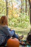 Femme s'asseyant dans la tente avec le potiron regardant des couleurs de chute photo libre de droits