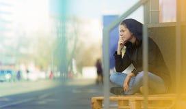 Femme s'asseyant dans la ville - photo de rue Photographie stock