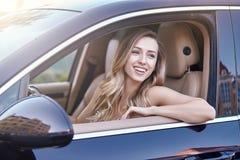 Femme s'asseyant dans la voiture et regardant loin photos stock